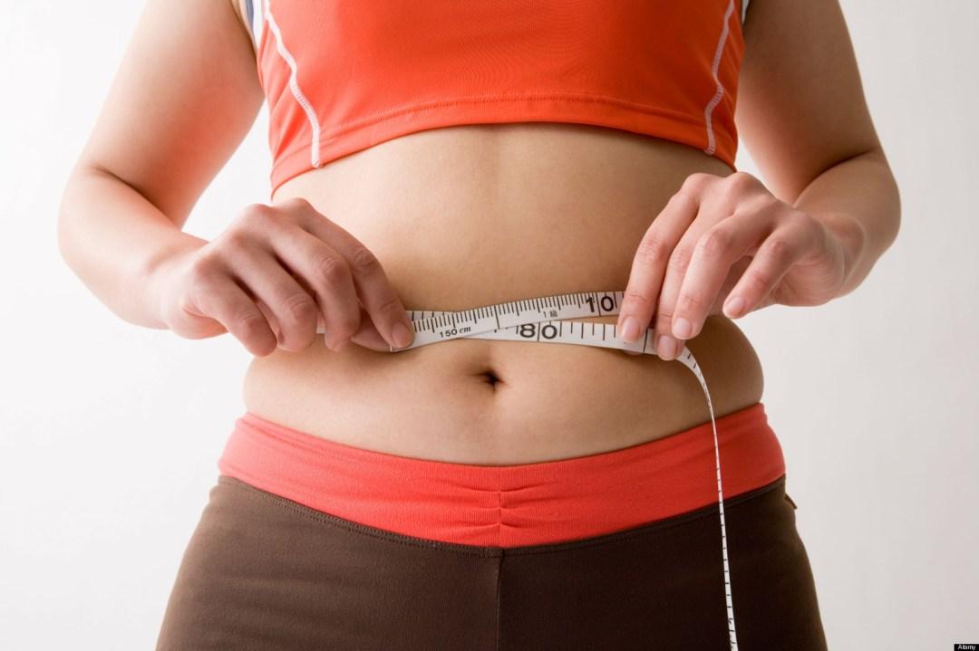 B3H3KA Mid adult woman measuring her waist